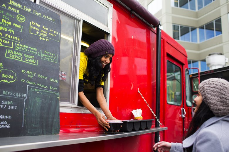 Shama Joshi (cq), of the food truck Roll OK Please, serves a customer during lunchtime on the campus of T-Mobile in Bellevue.