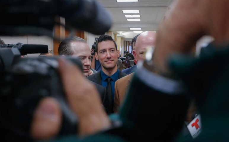 David Daleiden, center, one of the two anti-abortion activists indicted this year, addresses the media with attorneys Jared Woodfill, left, and Terry Yates after turning himself in to authorities on Feb. 4 in Houston. Bob Levey AP