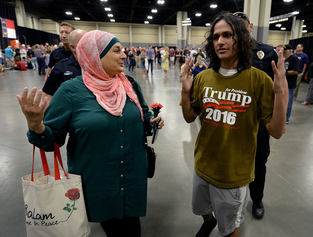 Rose Hamid, left, and Jake Anantha, right, are escorted from the Charlotte Convention Center in Charlotte, N.C., prior to a rally for GOP presidential candidate Donald Trump on Thursday, Aug. 18, 2016.