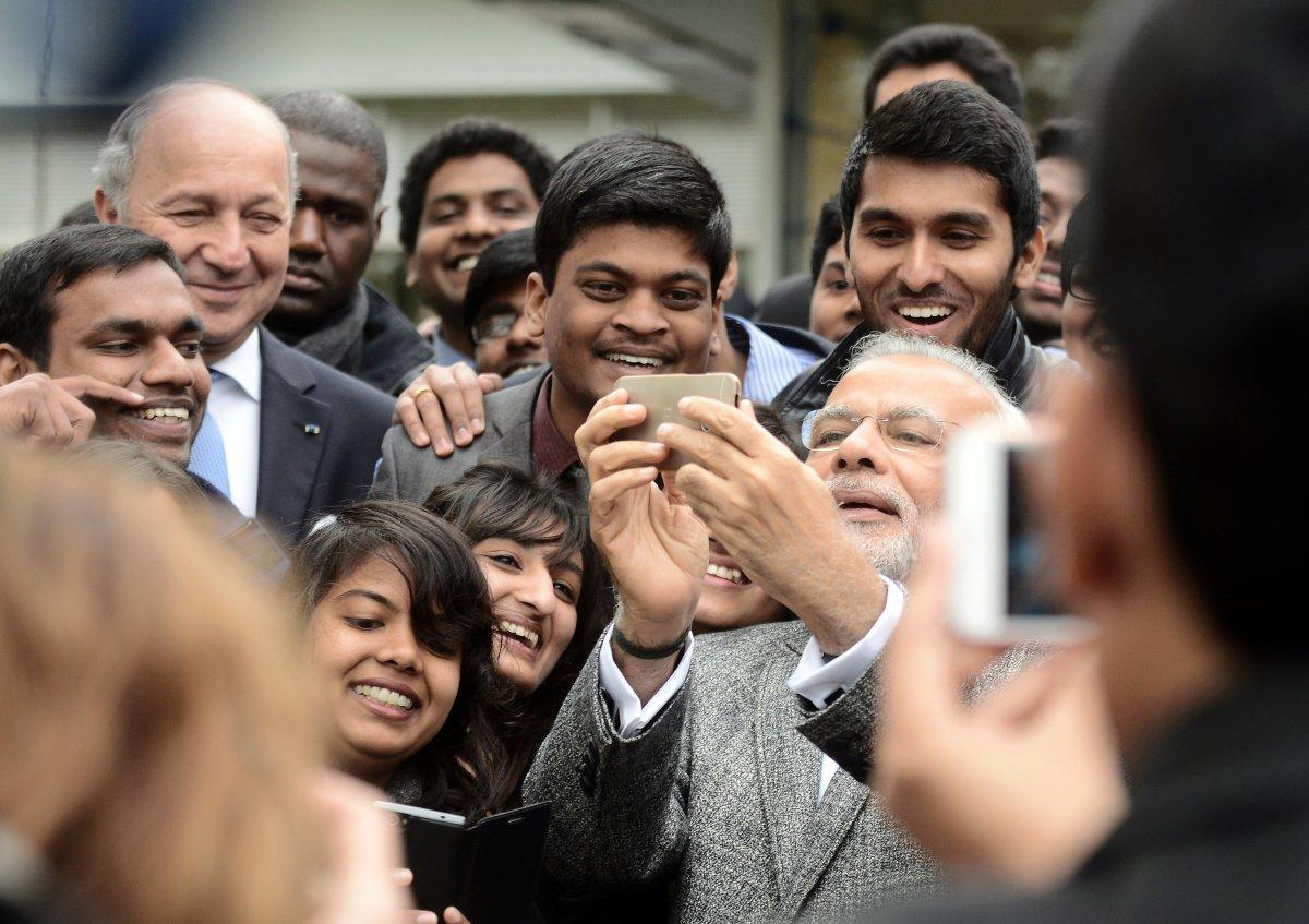 An April 2015 file photo from France showed Indian Prime Minister Narendra Modi taking a selfie with a group of Indian people studying abroad there. India suffered disproportionate selfie-deaths, a study found. (REMY GABALDA/AFP/GETTY IMAGES)
